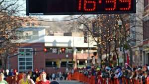 Liz Maloy crosses the finish line first Thursday Nov. 28, 2013, for the 6th time in Troy Turkey Trot 5K history in a winning time of 16:39 in Troy, N.Y.   (Skip Dickstein/Times Union)