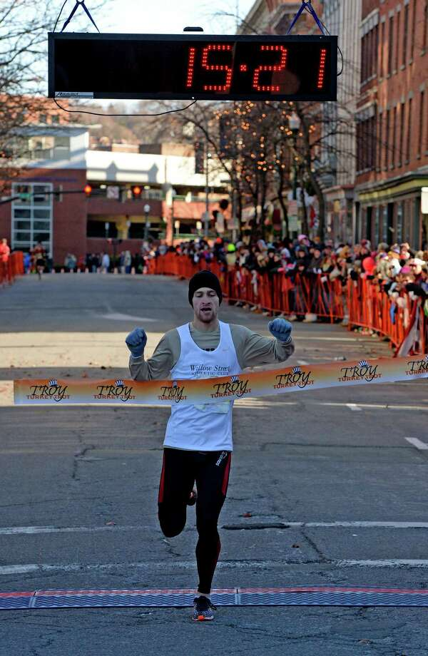 Men's winner Macky Lloyd crosses the finish line first Thursday Nov. 28, 2013, in the Troy Turkey Trot 5K in a winning time of 15:21 in Troy, N.Y.   (Skip Dickstein/Times Union) Photo: SKIP DICKSTEIN / 00024785A