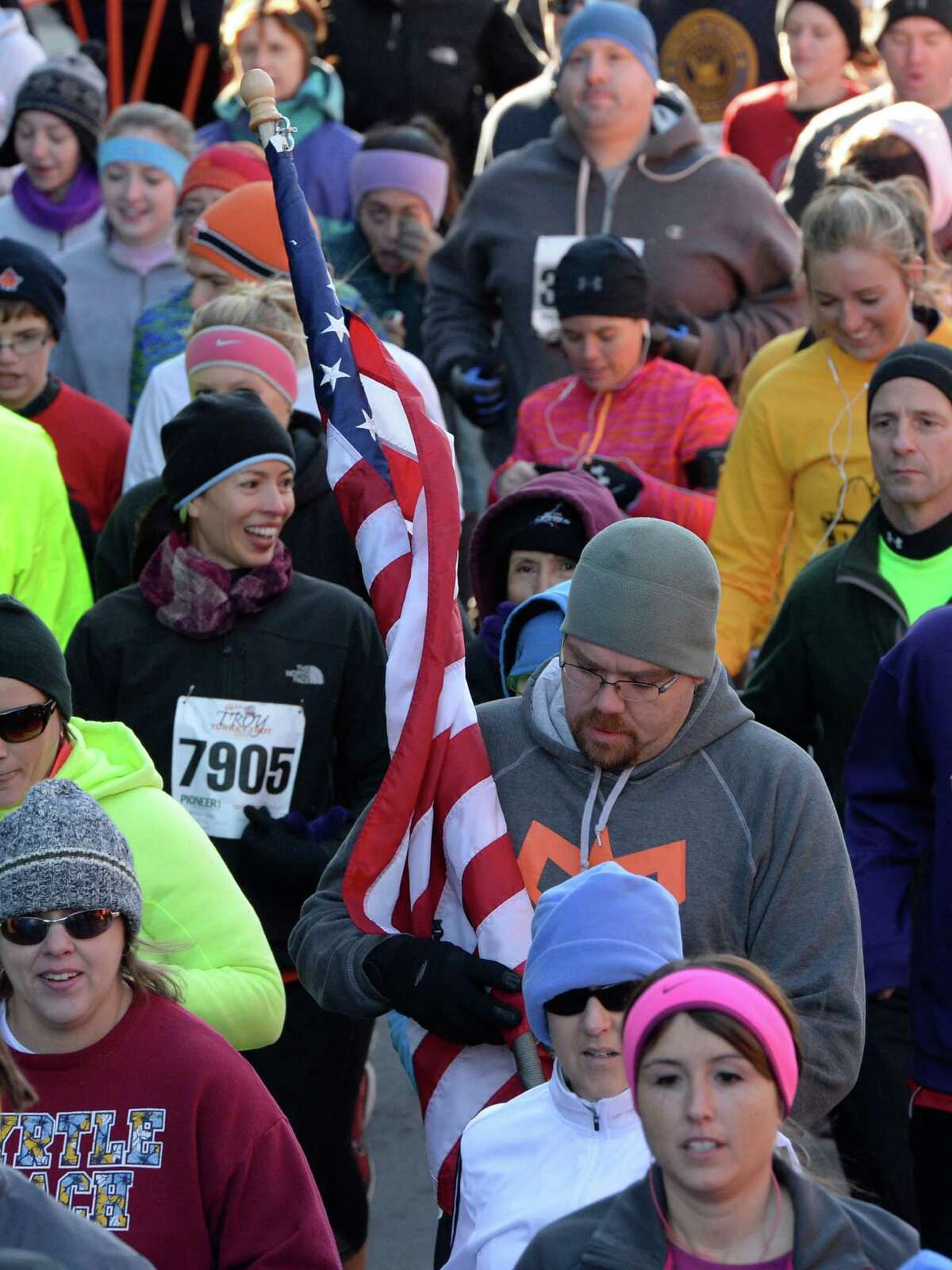 A runner carried an American Flag on the course Thursday Nov. 28, 2013, in the Troy Turkey Trot 5K in Troy, N.Y. (Skip Dickstein/Times Union)