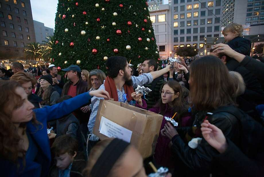 Chaim Sasonkin hands out candles before the 39th annual lighting of the Bill Graham Menorah in Union Square on Nov. 27, 2013. There have been lighting ceremony celebrating Hanukkah in Union Square since 1975. Photo: Douglas Zimmerman