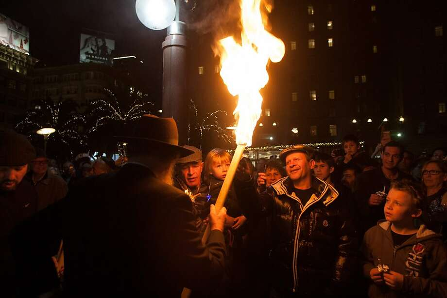Rabbi Yosef Langer carries a large torch to light the candles held by the  gathered crowd during the 39th annual lighting of the Bill Graham Menorah in Union Square on Nov. 27, 2013.  Hosted by and Chabad of San Francisco, there have been lighting ceremony celebrating Hanukkah in Union Square since 1975. Photo: Douglas Zimmerman