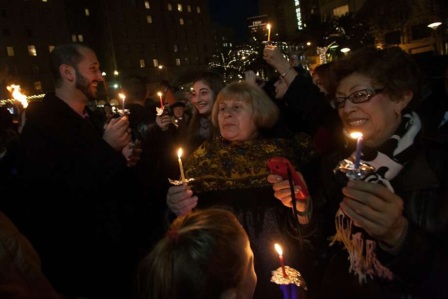 The gathered crowd holds candles during the 39th annual lighting of the Bill Graham Menorah in Union Square on Nov. 27, 2013.  Hosted by and Chabad of San Francisco, there have been lighting ceremony celebrating Hanukkah in Union Square since 1975. Photo: Douglas Zimmerman