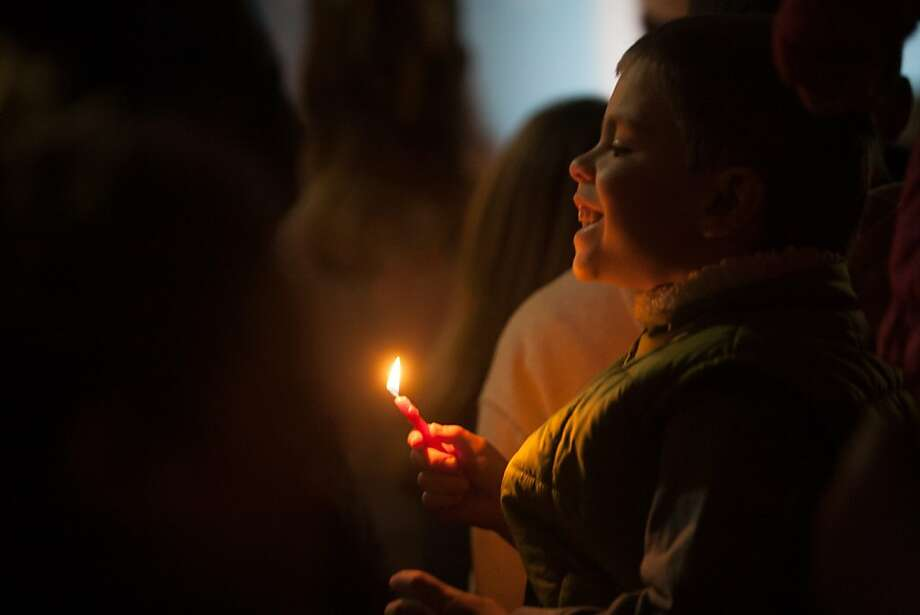 A young boy holds a candle during the 39th annual lighting of the Bill Graham Menorah in Union Square on Nov. 27, 2013.  Hosted by and Chabad of San Francisco, there have been lighting ceremony celebrating Hanukkah in Union Square since 1975. Photo: Douglas Zimmerman