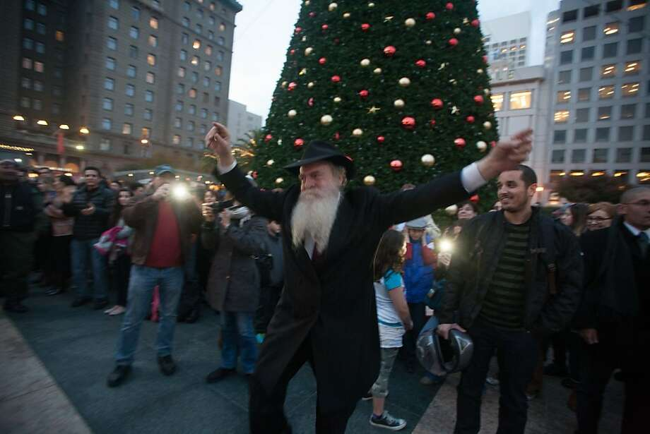 Rabbi Yosef Langer dances to music before the 39th annual lighting of the Bill Graham Menorah in Union Square on Nov. 27, 2013.  Hosted by and Chabad of San Francisco, there have been lighting ceremony celebrating Hanukkah in Union Square since 1975. Photo: Douglas Zimmerman