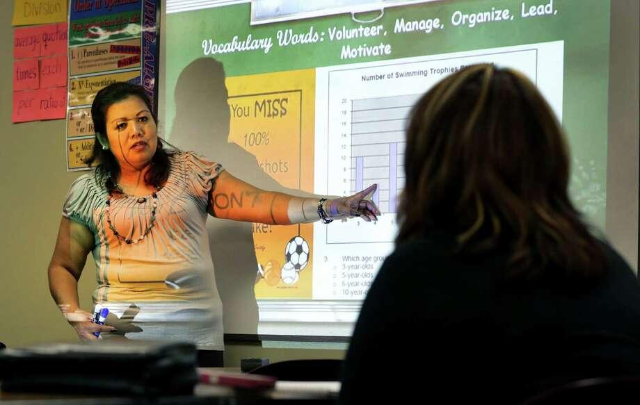 Maria Carmen Sanchez, a math and job skills instructor at WorkForce Solutions Alamo, teaches GED students. Photo: Bob Owen / San Antonio Express-News