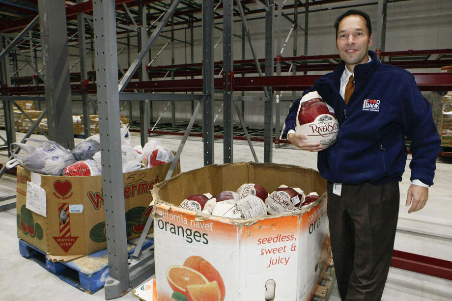 Eric Cooper, president and CEO of the San Antonio Food Bank, stands next to approximately 80 frozen turkeys in two bins. The holiday season is a time of giving, but the need lasts all year. Photo: Marvin Pfeiffer / San Antonio Express-News