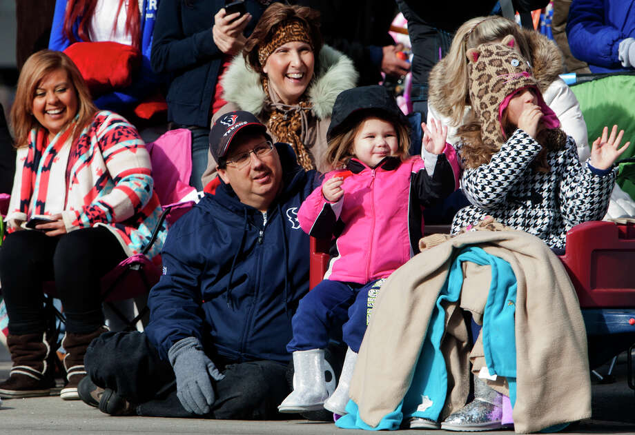 Orlando Turner, left, watches as his granddaughters Addisynn Turner, 3, center, and Becca Lanier, right, waves to participants during the 64th annual Thanksgiving Day Parade along Milam Street, Thursday, Nov. 28, 2013, in Houston. Photo: Cody Duty, Houston Chronicle / © 2013 Houston Chronicle