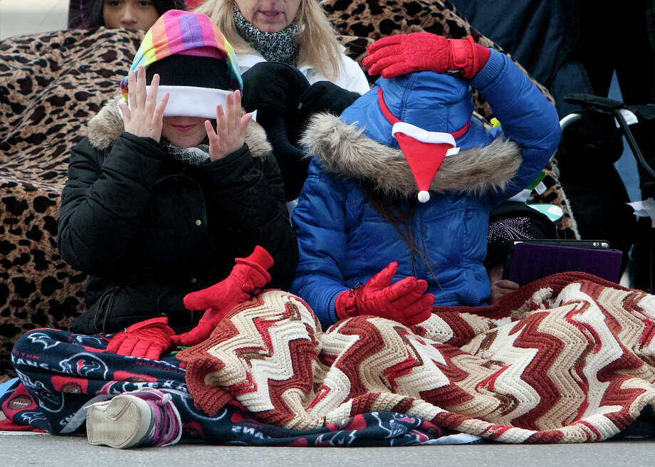 Kailee Frost, 11, left, and her cousin Rylee Frost, right, 9, adjust their warm weather gear as they wait for the start of the 64th annual Thanksgiving Day Parade along Walker Street Thursday, Nov. 28, 2013, in Houston. Photo: Cody Duty, Houston Chronicle / © 2013 Houston Chronicle