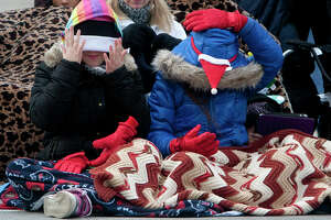 Kailee Frost, 11, left, and her cousin Rylee Frost, right, 9, adjust their warm weather gear as they wait for the start of the 64th annual Thanksgiving Day Parade along Walker Street Thursday, Nov. 28, 2013, in Houston.