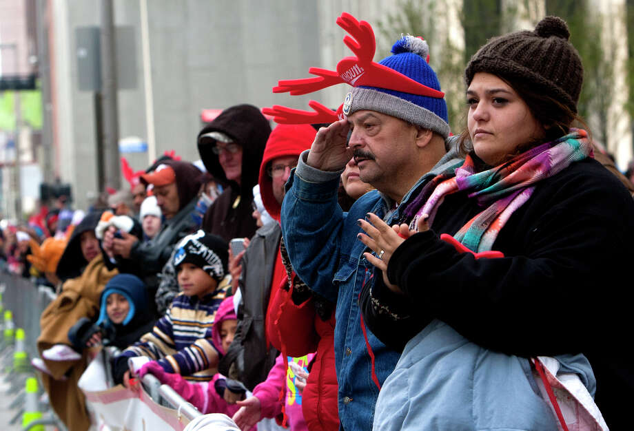 Jeff Smith salutes to veterans as he stands with his daughter Amy Smith, right, during the 64th annual Thanksgiving Day Parade along Smith Street, Thursday, Nov. 28, 2013, in Houston. Photo: Cody Duty, Houston Chronicle / © 2013 Houston Chronicle