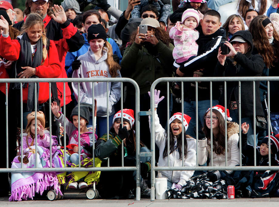 Spectators wave to participants in the 64th annual Thanksgiving Day Parade along Walker Street, Thursday, Nov. 28, 2013, in Houston. Photo: Cody Duty, Houston Chronicle / © 2013 Houston Chronicle