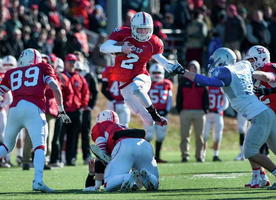 Fairfield Prep quarterback Colton Smith leaps over one of his linemen while trying to pick up some yards during a Thanksgiving Day football game against West Haven high school played at Alumni field, Fairfield University, Fairfield, CT on Thursday, November 28th, 2013. Photo: Mark Conrad / Connecticut Post Freelance