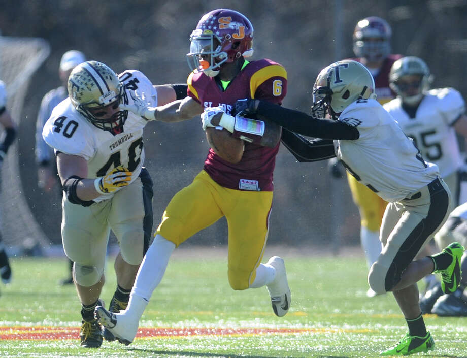 St. Joseph's Mufasa Abdul-Basir tries to shake off Trumbull defenders Andrew Marino, left, and Jamar Robinson during the annual Thanksgiving Day football game Thursday, Nov. 28, 2013 at St. Joseph High School in Trumbull, Conn. Photo: Autumn Driscoll / Connecticut Post