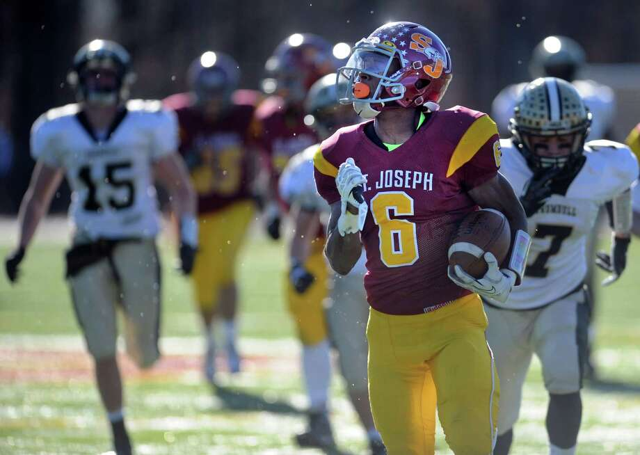 St. Joseph's Mufasa Abdul-Basir stays ahead of Trumbull during the annual Thanksgiving Day football game Thursday, Nov. 28, 2013 at St. Joseph High School in Trumbull, Conn. Photo: Autumn Driscoll / Connecticut Post