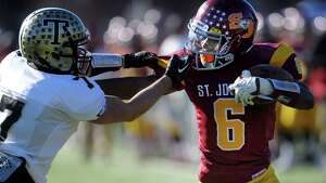 St. Joseph's Mufasa Abdul-Basir fends off Trumbull's Thomas Hayduck on his way to a touchdown during the annual Thanksgiving Day football game Thursday, Nov. 28, 2013 at St. Joseph High School in Trumbull, Conn.