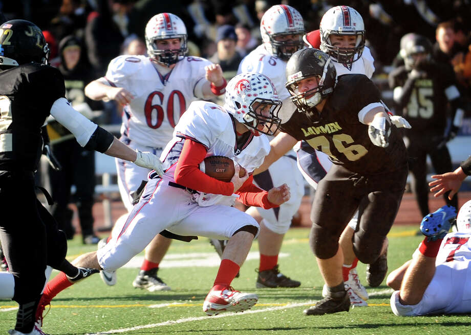 Foran's Jake Kasuba runs up the middle towards  Law defender Mike DiBartolomeo in the first half of their Thanksgiving Day matchup at Jonathan Law High School in Milford, Conn. on Thursday, November 28, 2013. Photo: Brian A. Pounds / Connecticut Post