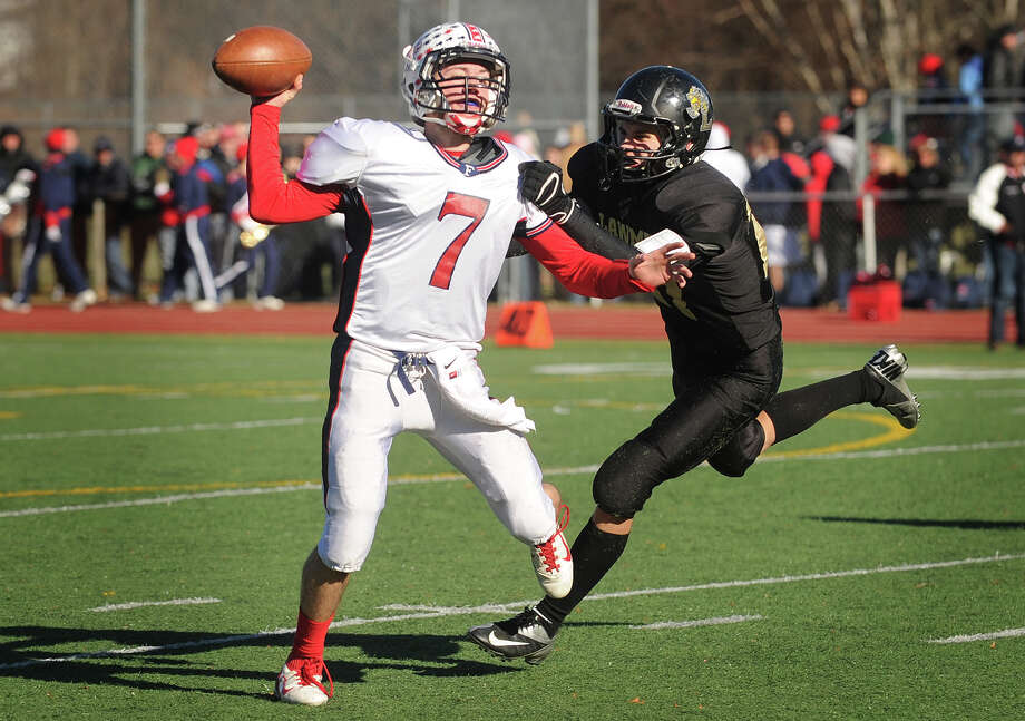 Foran quarterback Jake Kasuba gets a pass away while being pursued by Law defender Max German in the first half of their Thanksgiving Day matchup at Jonathan Law High School in Milford, Conn. on Thursday, November 28, 2013. Photo: Brian A. Pounds / Connecticut Post