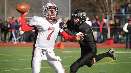 Foran quarterback Jake Kasuba gets a pass away while being pursued by Law defender Max German in the first half of their Thanksgiving Day matchup at Jonathan Law High School in Milford, Conn. on Thursday, November 28, 2013.
