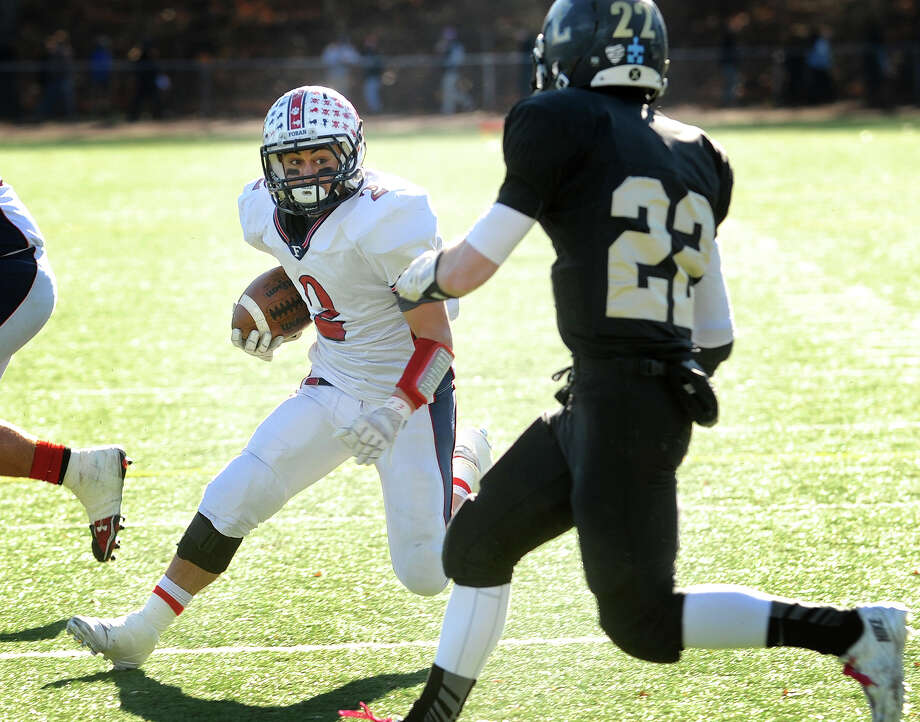 Foran's Nick Weissauer runs for the game's opening touchdown as he is pursued by Law defender Timmy Maher in the first half of their Thanksgiving Day matchup at Jonathan Law High School in Milford, Conn. on Thursday, November 28, 2013. Photo: Brian A. Pounds / Connecticut Post
