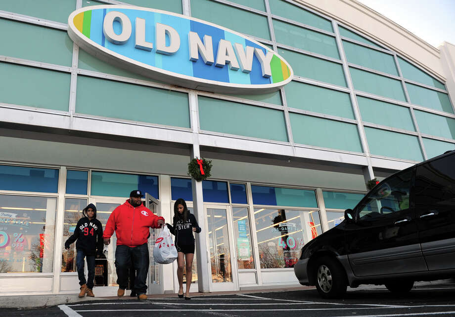 Oswaldo Perez Jr., of Bridgeport, leaves the Old Navy store with his children after looking for Thanksgiving Day deals in Fairfield, Conn. on Thursday November 28, 2013. From left to right is son Rafael Cruz, 11, Oswaldo Perez, his daughter Stephanie, 13, and not pictured is his other son Oswaldo Perez III, 13. Photo: Christian Abraham / Connecticut Post
