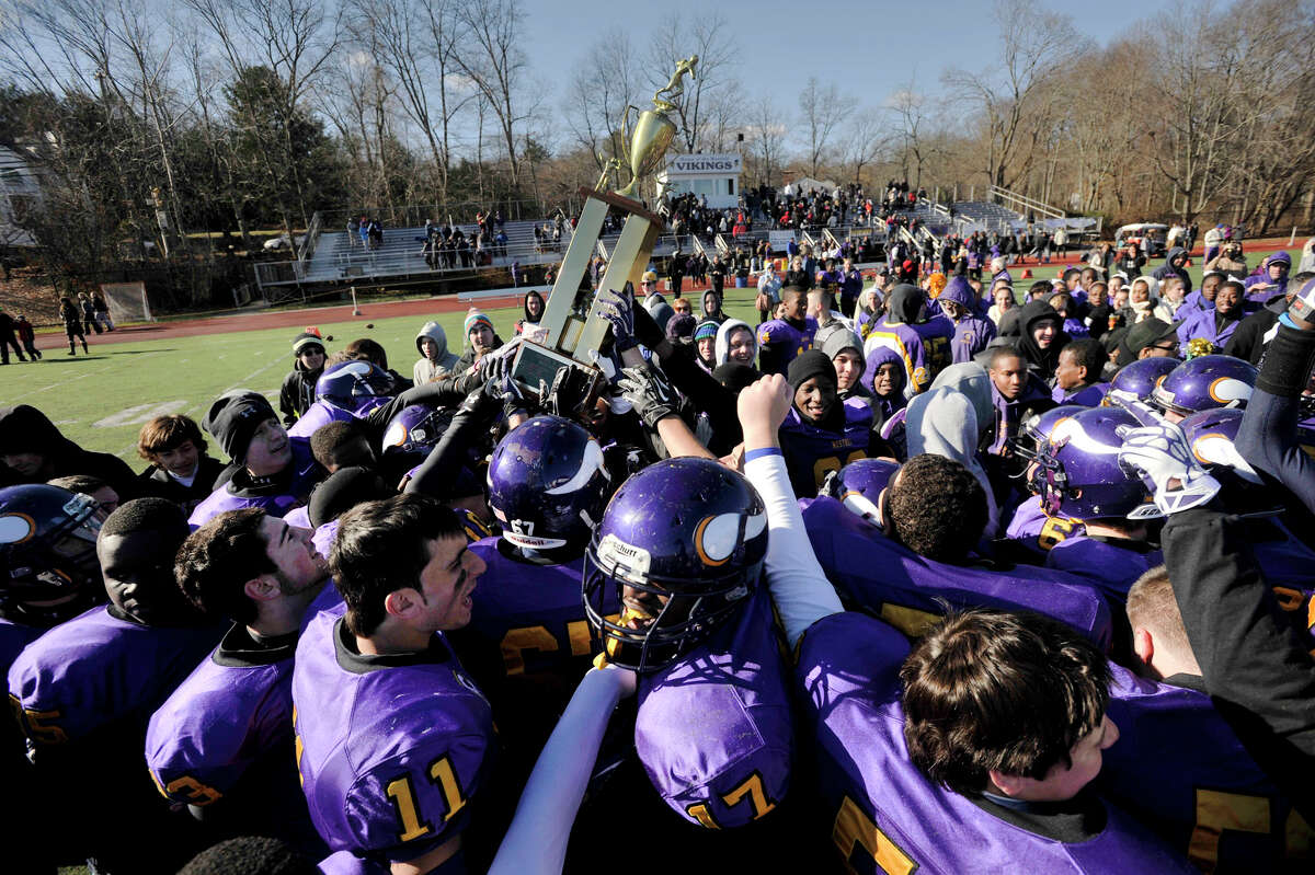 The Westhill football team raises the Frank Robotti after defeating Stamford High, 40-0, at Westhill High School in Stamford, Conn., on Thanksgiving Day, Thursday, Nov. 28, 2013.