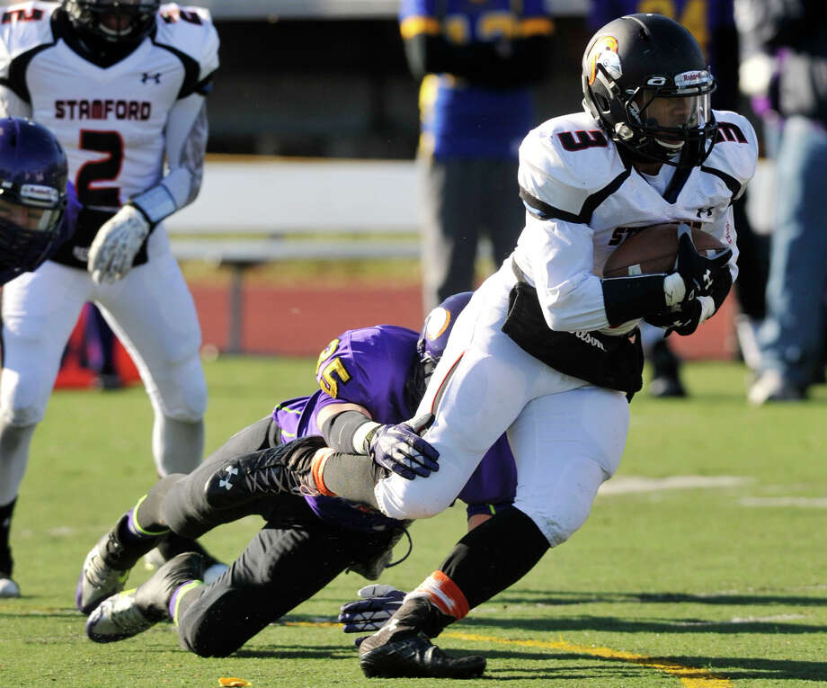 Westhill's Zac Cowit attempts to bring down Stamford's Cameron Webb during their game at Westhill High School in Stamford, Conn., on Thanksgiving Day, Thursday, Nov. 28, 2013. Westhill beat Stamford, 40-0 to win the City Championship. Photo: Jason Rearick / Stamford Advocate