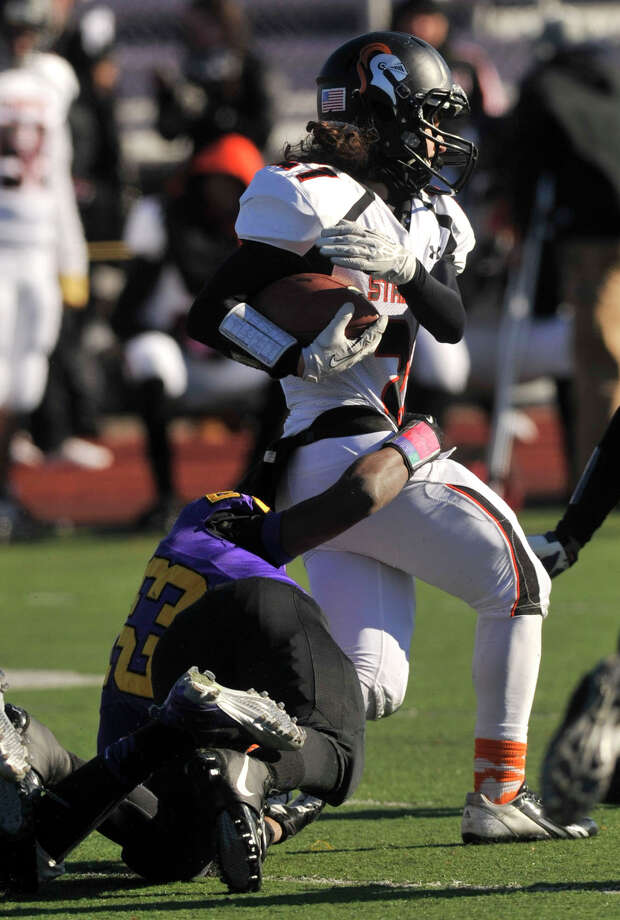 Westhill's Jeff Glover attempts to bring down Stamford's Anthony Pearson during their game at Westhill High School in Stamford, Conn., on Thanksgiving Day, Thursday, Nov. 28, 2013. Westhill beat Stamford, 40-0 to win the City Championship. Photo: Jason Rearick / Stamford Advocate