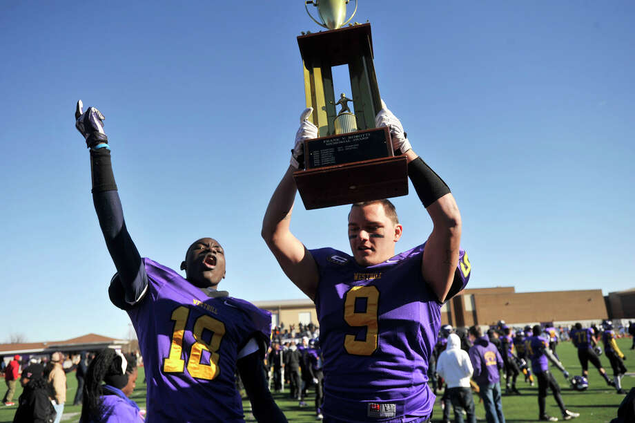 Westhill's Emmanuel Revange, left, and Dennis Hart-Lima celebrate their 40-0 win over Stamford at Westhill High School in Stamford, Conn., on Thanksgiving Day, Thursday, Nov. 28, 2013. Dennis Hart-Lima holds the Frank Robotti trophy. Photo: Jason Rearick / Stamford Advocate