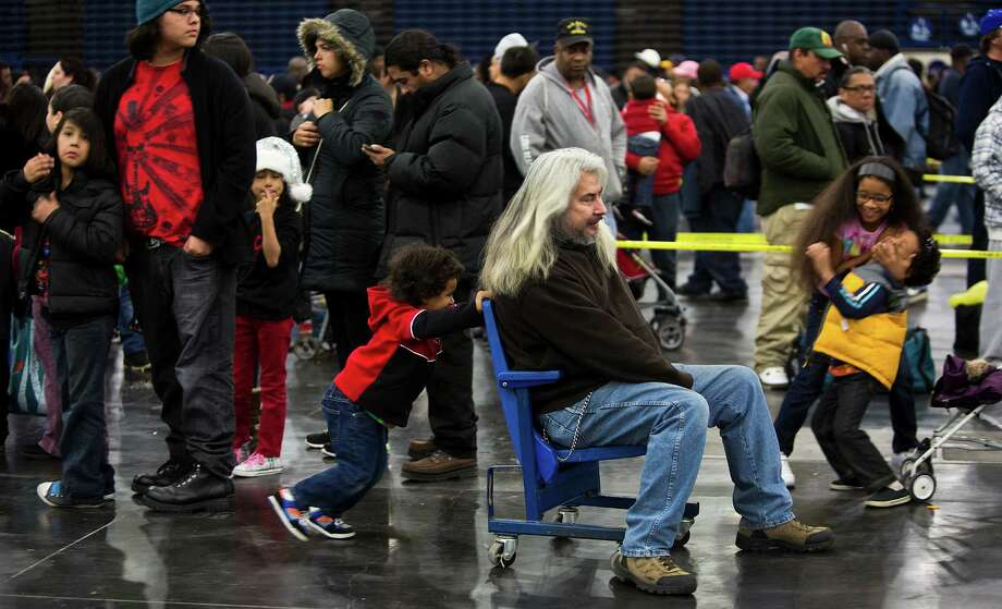 Jermiah Williams, 4, gives a push to his grandfather Benigno Rodriguez while Williams' siblings Elissa Williams and Adrian Williams play on the right. The family wait for their turn to get a meal together at the 35th Annual Thanksgiving Big Super Feast in Houston, Thursday, Nov. 28, 2013. Photo: Marie D. De Jesus, Houston Chronicle / © 2013 Houston Chronicle