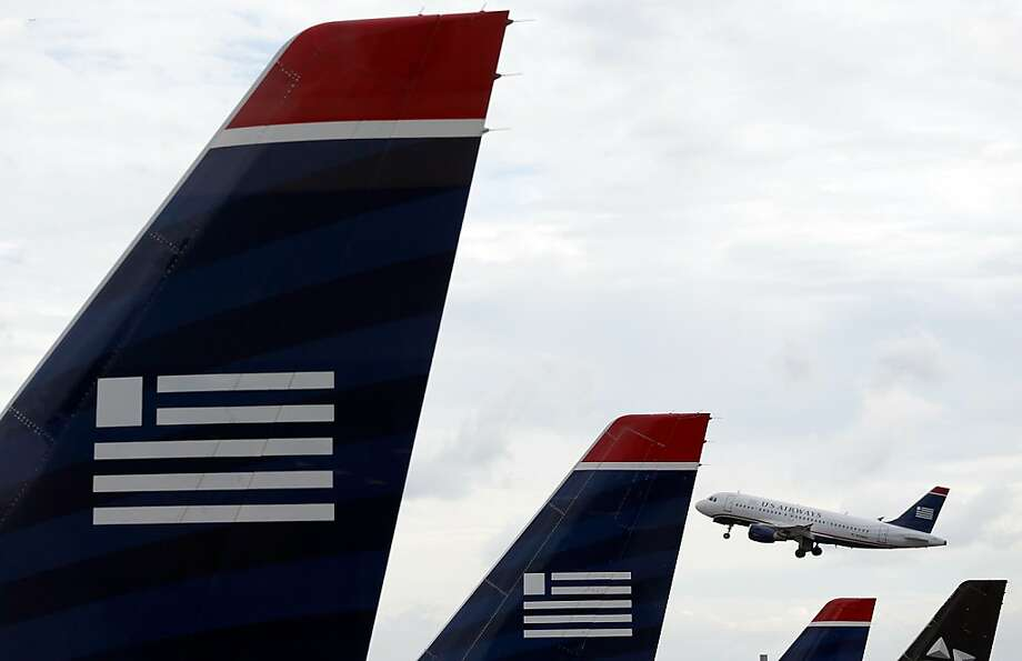 File: A bankruptcy judge approved the antitrust settlement between the Justice Department and AMR Corp. and US Airways Group Inc.  clearing the last step to a deal that will create the world's largest airline. ARLINGTON, VA - AUGUST 13:  A US Airways jet takes off at Ronald Reagan Washington National Airport August 13, 2013 in Arlington, Virginia. The U.S. Justice Department, and attorneys general from six states, filed legal actions today attempting to prevent the planned merger of US Airways and American Airlines as a violation of antitrust law.  (Photo by Win McNamee/Getty Images) Photo: Win McNamee, Getty Images