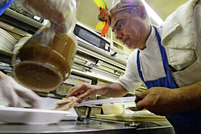 Chef John Marzilli puts the finishing touches on a turkey dinner to be distributed by members of the Twin Bridges Rotary to those in need Thursday afternoon Nov. 28, 2013, at Salty's Pub in Halfmoon, N.Y. (Skip Dickstein / Times Union)