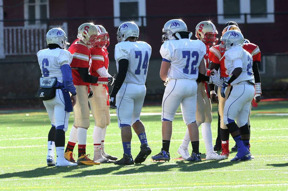 Members of the Bunnell High School and Stratford High School shake hands at the start of Thanksgiving match-up at Penders Field in Stratford. Bunnell would win 12-10.
