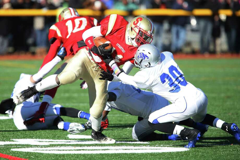 Stratford High School's #11 David Davidson escapes the tackle and makes the first down against  Bunnell High School's #30 Brett Bogdwicz during first half action on Thursday's Thanksgiving match-up. Bunnell would win 12-10. Photo: Mike Ross / Mike Ross Connecticut Post freelance - @www.mikerossphoto.com