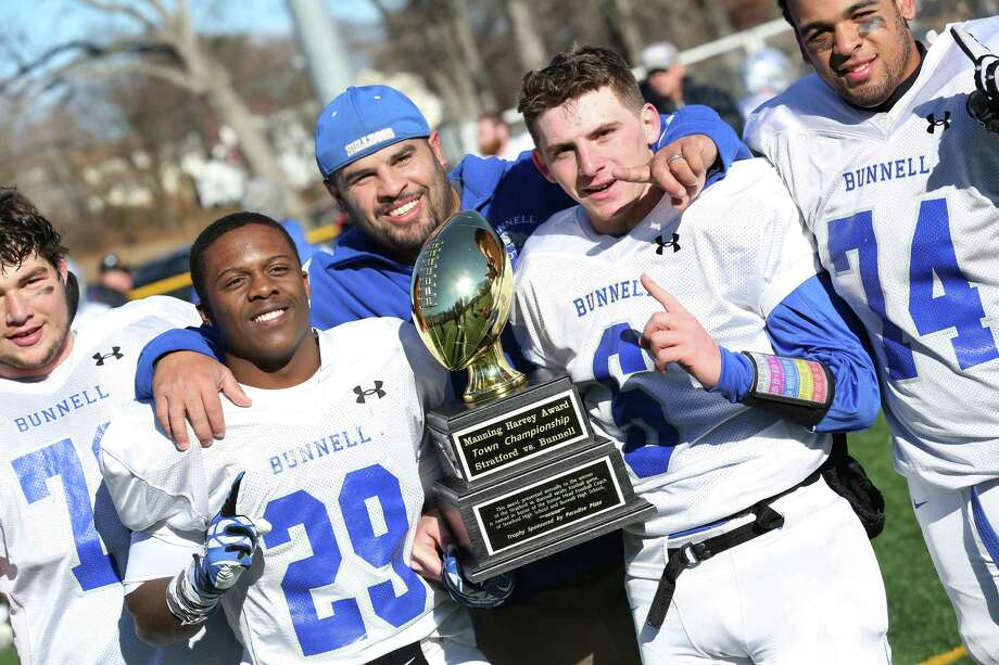 Bunnell High School's head coach Doug Cotto and players #72 Benjamin Ruskin, #29 Andrick Bernadel, #6 Nolan Aurelia and #74 Anthony Johnson pose with the Manny Harvey Award after winning the Thursday Thanksgiving match-up against Stratford High School. Photo: Mike Ross / Mike Ross Connecticut Post freelance - @www.mikerossphoto.com