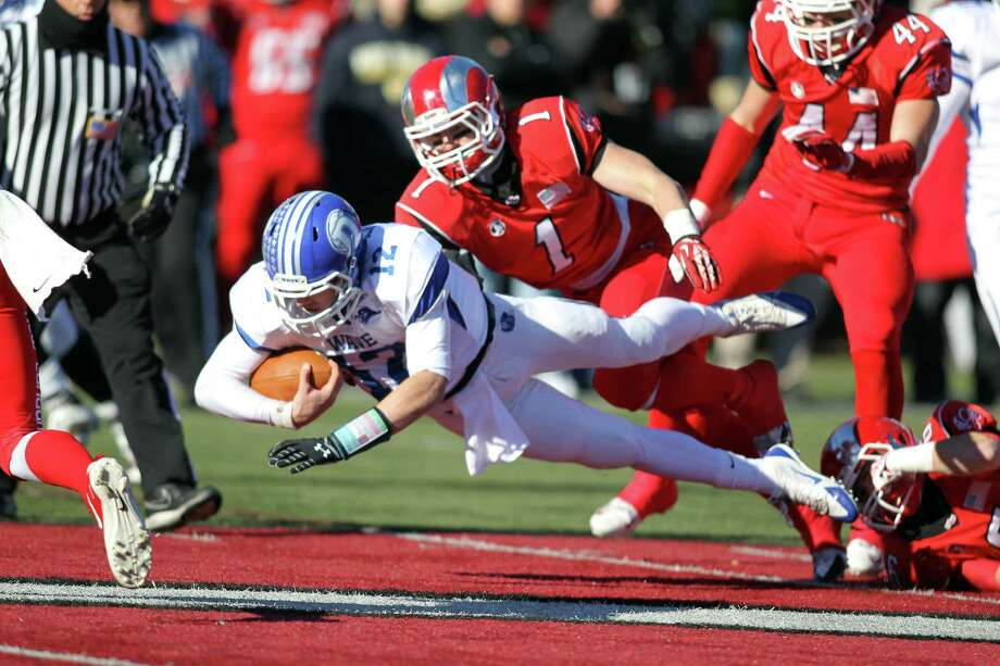 Darien quarterback Silas Wyper scores a touchdown in front of New Canaan's Michael Root (1) and Zach Allen (44). Photo: J. Gregory Raymond / Stamford Advocate Freelance