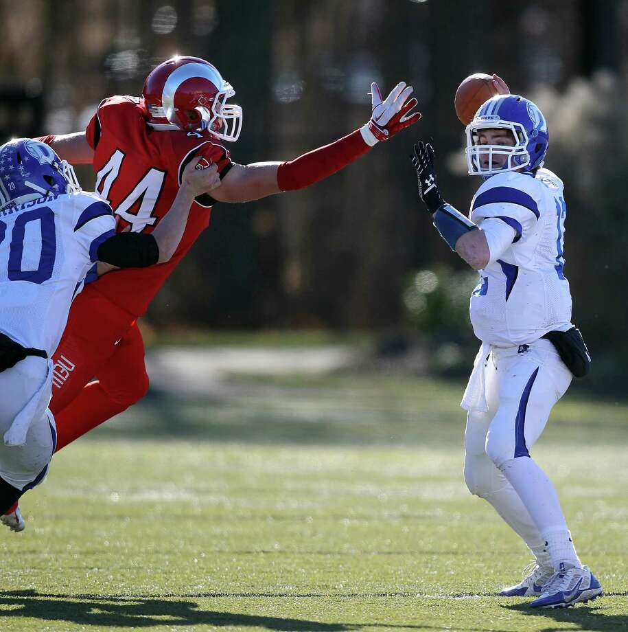 New Canaan's Zachary Allen is about to swipe the football away from Darien's Silas Wyper for a score against Darien in the annual Thanksgiving Turkey Bowl in New Canaan on Thursday. Darien came out on top, 28-24. J. Gregory Raymond for The Advocate Photo: J. Gregory Raymond / Stamford Advocate Freelance;  © J. Gregory Raymond