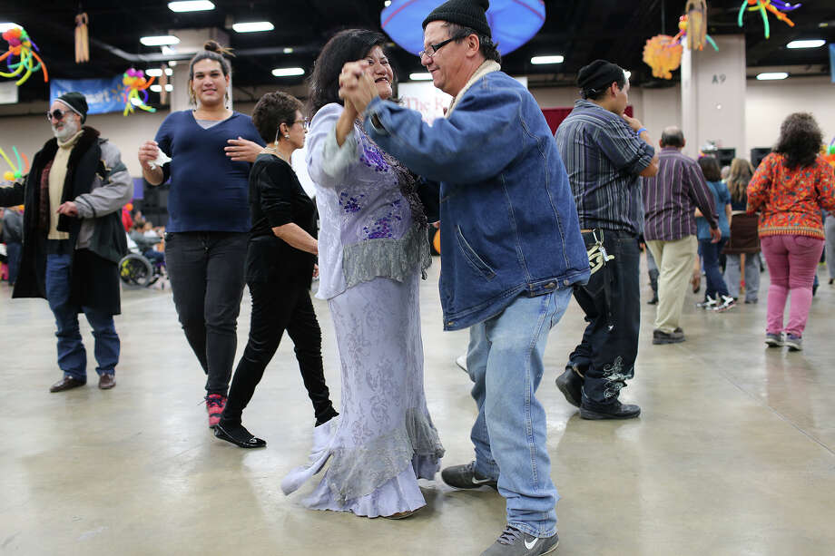 Martina Muñoz and Andres Perez dance at the Henry B. Gonzalez Convention Center during the 34th annual Raul Jimenez Thanksgiving Dinner, Thursday, Nov. 28, 2013. Photo: JERRY LARA, San Antonio Express-News / © 2013 San Antonio Express-News