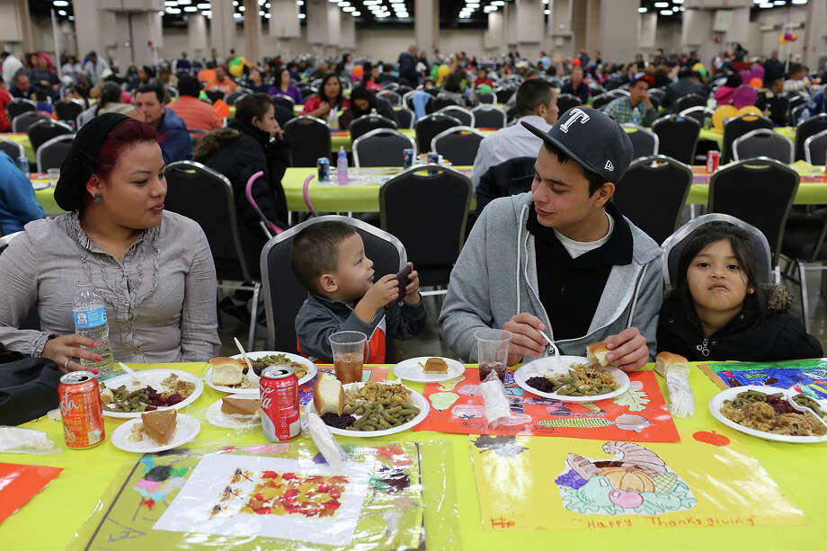 Dominick Medina, 3, second from left, photographs his family gathered at the Henry B. Gonzalez Convention Center for the 34th annual Raul Jimenez Thanksgiving Dinner, Thursday, Nov. 28, 2013. From left, are Wendy Palacios, Michael Palacios and Natasha Palacios. Photo: JERRY LARA, San Antonio Express-News / © 2013 San Antonio Express-News