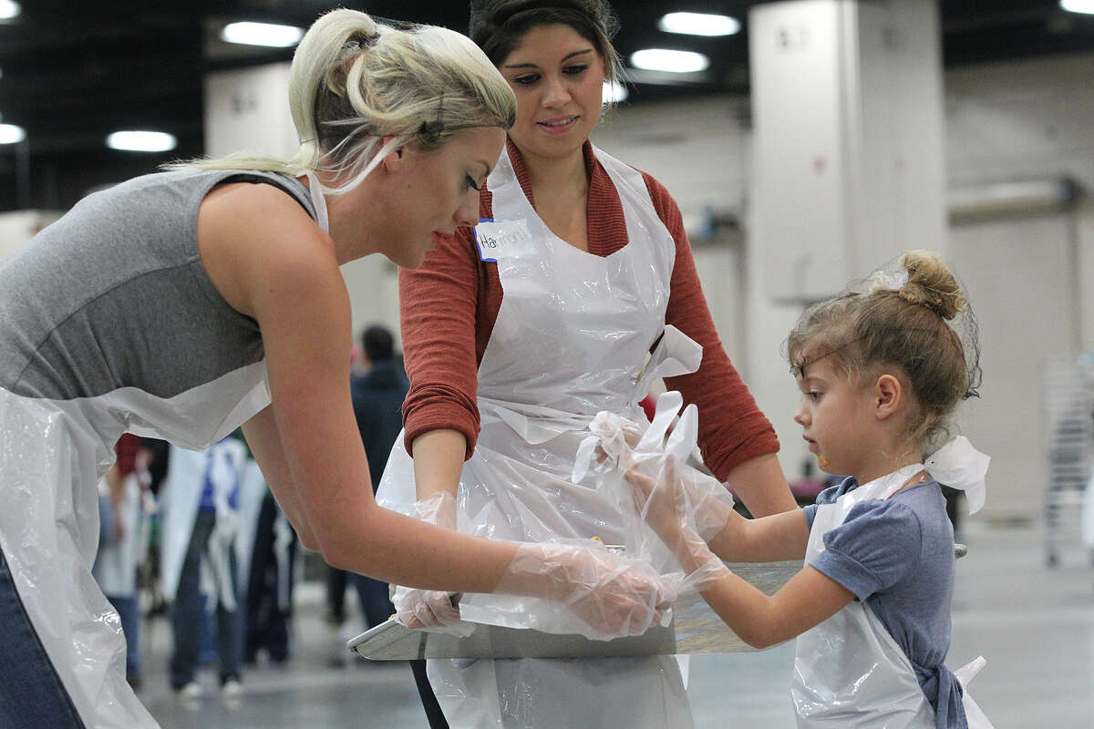 Celeste Jenkins, 5, right, gets help with glove from her mother, Ciara Ford, left, as they and Harmony Campbell prepare to serve slices of pumpkin pie at the Henry B. Gonzalez Convention Center during the 34th annual Raul Jimenez Thanksgiving Dinner, Thursday, Nov. 28, 2013.