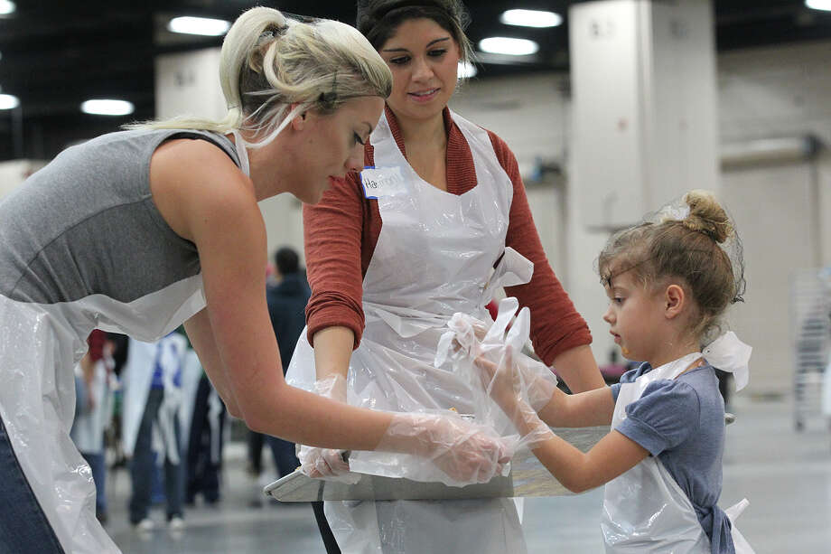 Celeste Jenkins, 5, right, gets help with glove from her mother, Ciara Ford, left, as they and Harmony Campbell prepare to serve slices of pumpkin pie at the Henry B. Gonzalez Convention Center during the 34th annual Raul Jimenez Thanksgiving Dinner, Thursday, Nov. 28, 2013. Photo: Jerry Lara, San Antonio Express-News / © 2013 San Antonio Express-News