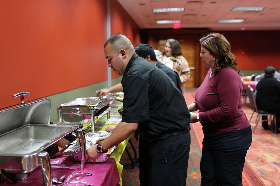 Jacob Rodriguez works the VIP section at the Henry B. Gonzalez Convention Center during the 34th annual Raul Jimenez Thanksgiving Dinner, Thursday, Nov. 28, 2013. Over 4,000 thousand volunteers were expected to serve 20,000 guest. Last year, 9,400 pounds of turkey, 32,000 dinner rolls and 12,500 pounds of stuffing were served. To the right of Rodriguez is the late Jimenez's daughter, Patricia Jimenez. Photo: JERRY LARA, San Antonio Express-News / © 2013 San Antonio Express-News