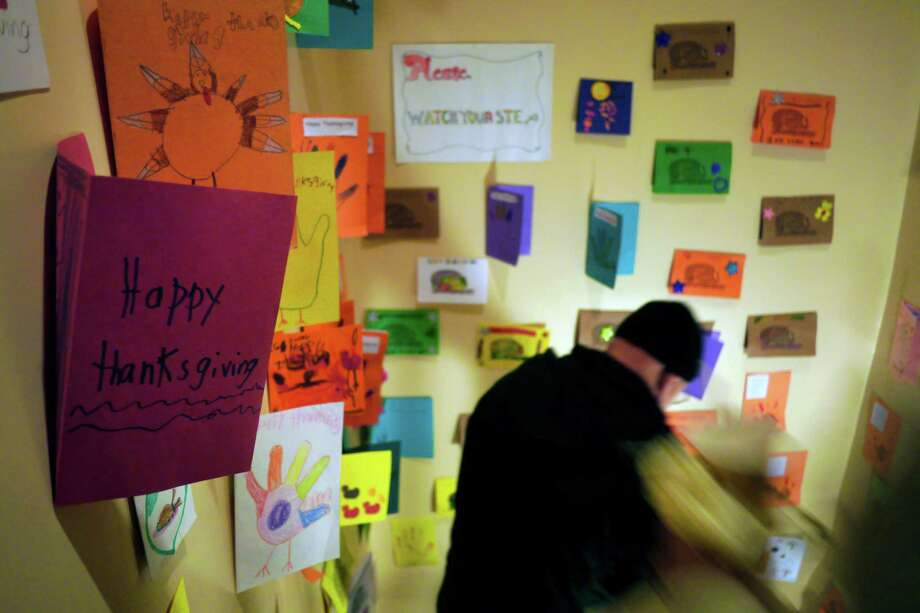 Thanksgiving Day cards are used to decorate the walls as people head down stairs for desert  at the annual Equinox Thanksgiving Day meal at the First Presbyterian Church on Thursday, Nov. 28, 2013 in Albany, NY.  Each year the meal feeds around 500 people.  Equinox also delivers meals to people around the Capital Region.  This year organizers said that about 9,500 meals were delivered on Thanksgiving morning by volunteers.    (Paul Buckowski / Times Union) Photo: Paul Buckowski / 00024808A