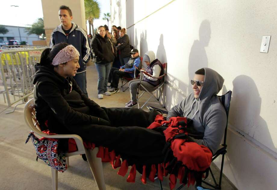 Christian Rosales and Bryan Bustos attempt to stay warm as they wait outside a Best Buy in hopes of great shopping specials on Thursday, Nov. 28, 2013, in Webster. Photo: J. Patric Schneider, For The Chronicle / © 2013 Houston Chronicle