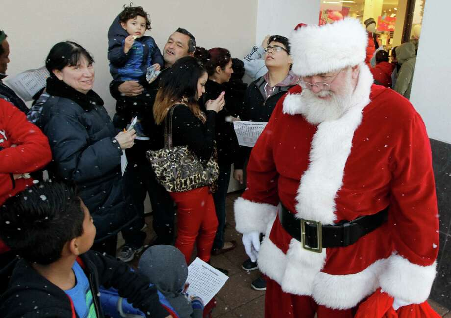 Santa visits with shoppers as they wait in line outside a Palais Royal at the Meyerland shopping center on Thursday, Nov. 28, 2013, in Houston. Photo: J. Patric Schneider, For The Chronicle / © 2013 Houston Chronicle