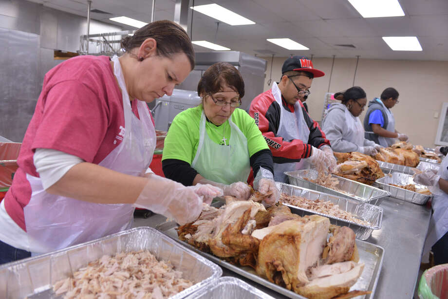 Volunteers Jeanette Pollock, Isabele Faulkner and Abraham Rodriguez pull meat from turkeys Monday, Nov. 25, 2013, in preparation for the annual Raul Jimenez Thanksgiving Dinner Thursday. Over 500 turkeys were cooked. Photo: Robin Jerstad, For The San Antonio Express-News