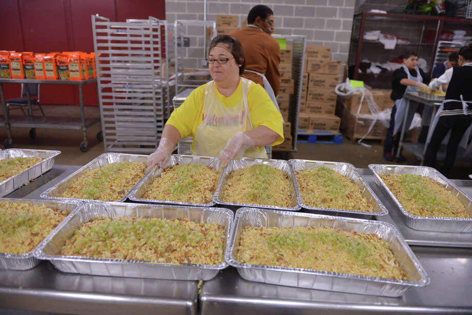 Volunteer Mary Rodriguez moves pans of dressing along to the next station Monday, Nov. 25, 2013, in the RK Group kitchens at the Henry B. Gonzalez Convention Center in preparation for the annual Raul Jimenez Thanksgiving Dinner. Photo: Robin Jerstad, For The San Antonio Express-News