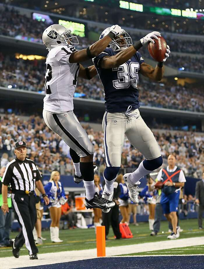 Dallas' Brandon Carr jumps in front of Oakland's Jacoby Ford for a deflating fourth-quarter interception in the end zone. Photo: Ronald Martinez, Getty Images