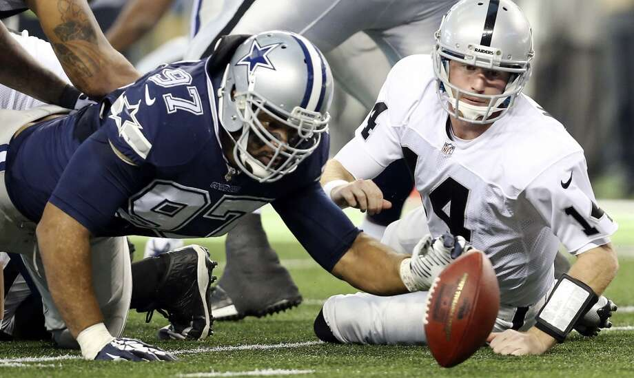 Dallas Cowboys' Jason Hatcher and Oakland Raiders Matt McGloin chase after a fumble during first half action Thursday Nov. 28, 2013 at AT&T Stadium in Arlington, Tx. Photo: Edward A. Ornelas, San Antonio Express-News