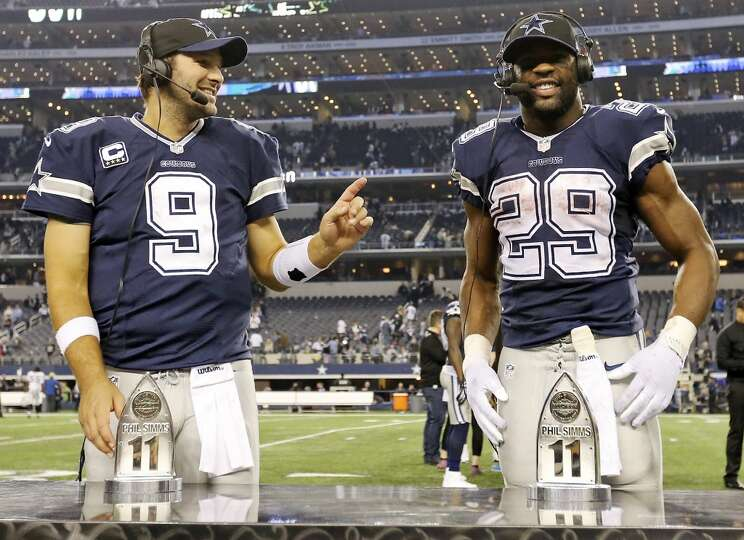 Dallas Cowboys' Tony Romo (left) jokes with teammate DeMarco Murray during an interview after the ga