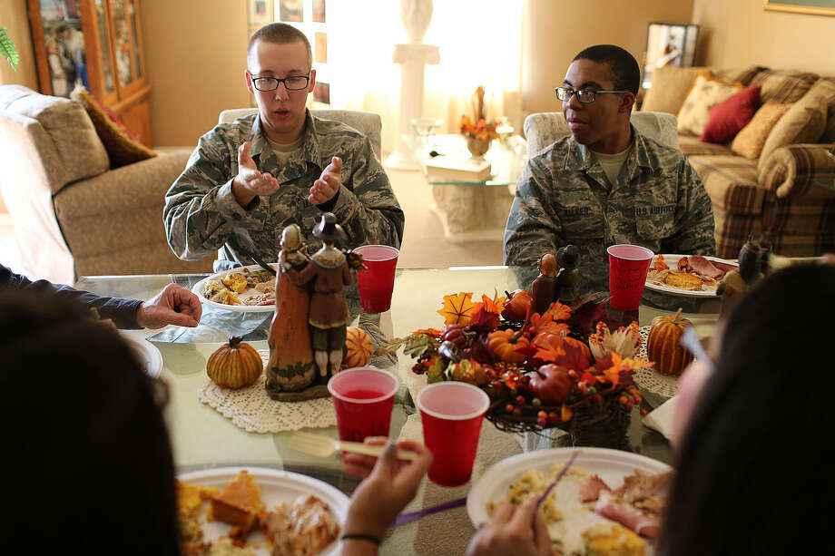 During Thanksgiving dinner Thursday, Joint-Base San Antonio Lackland trainees Kyle Nadeau (left), 19, of Somerset, Mass., and Michael Walker, 18, from Baltimore, entertain their hosts, the Ruben and Yolanda Garza family, with stories from their training. Photo: Jerry Lara / San Antonio Express-News